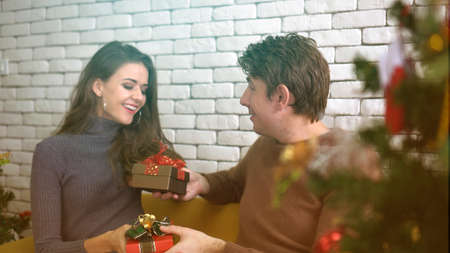 Couple exchage christmas gift care and happy relation celebrating holiday