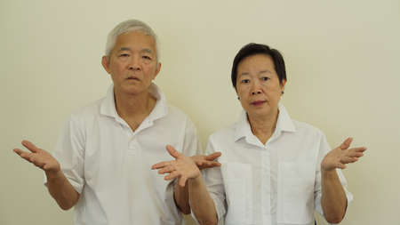 Asian elder old couple unhappy angry with situation with copy space 스톡 콘텐츠