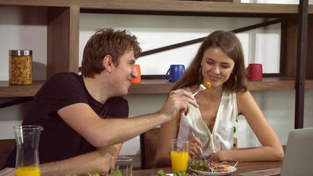 White couple feeding and have fun conversation while eating salad Banco de Imagens