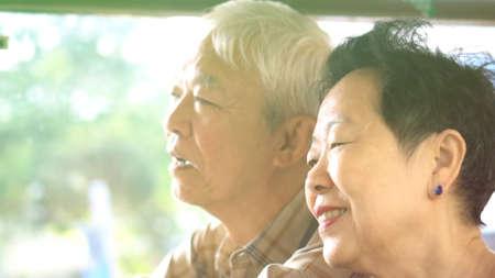 Asian elder couple have fun on public transportation morning sun light together