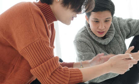Two Asian friend sharing application and information on mobile phone