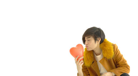 Cool modern Asian woman happy in love holding red heart ballon with copy space