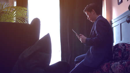 Asian executive manager  businessman in suit working through smartphone from luxury home Фото со стока