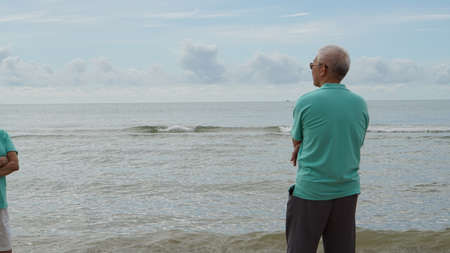 Asian senior elder man standing alone at the beach thinking about life