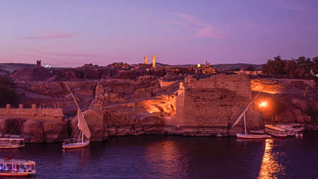 Nile river at sunset evening beautiful sky with ruin wall and lighting with felluca boat