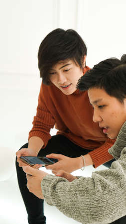 Southeast Asian friends playing smart phone togetehr in winter cloth Archivio Fotografico