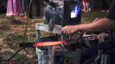 Blacksmith making hitting sword handmade traditional craftmanship show event