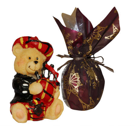 bagpipes: Scottish bear toy playing on bagpipes with a gift