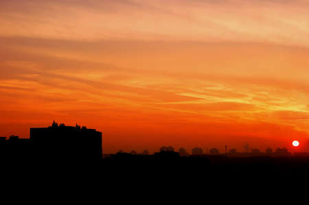 red sunset in the city with the accurate line of buildings Фото со стока