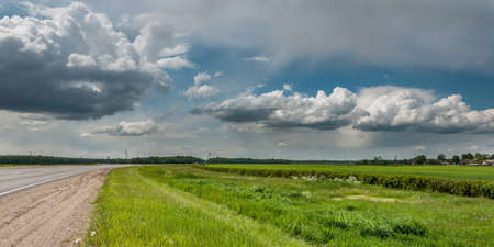 non stock: interesting picturesque rural landscape. country asphalt road, green meadow, beautiful cloudy sky, village