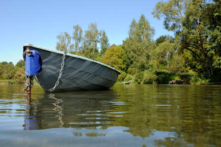 non stock: boat is moored by a chain to a column in shallow water near the coast of the lake