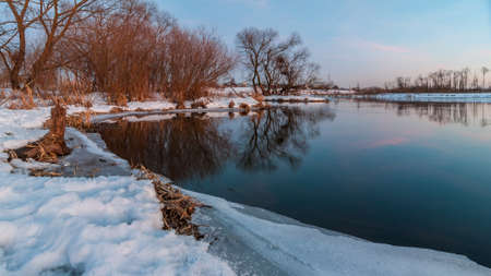 beautiful evening winter landscape. February thaw. Coast of the river with the ice edge and the vegetation under the snow