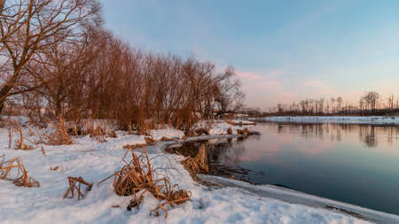 Beautiful evening winter landscape. February thaw. Coast suburb with river ice edge and the vegetation under the snow