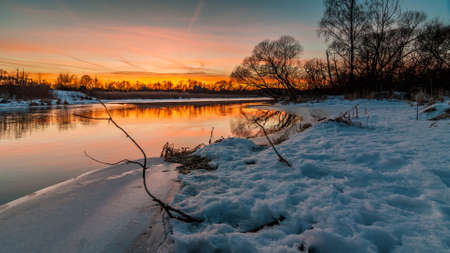 Beautiful evening winter landscape. red sunset over the river from the edge of the ice and vegetation under the snow. February thaw Stock Photo