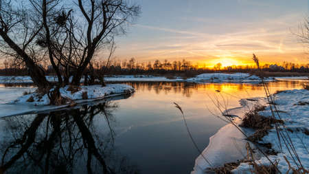 Beautiful evening winter landscape. picturesque orange glow of sunset over the river to the coast suburb under snow and ice edge. February thaw Stock Photo