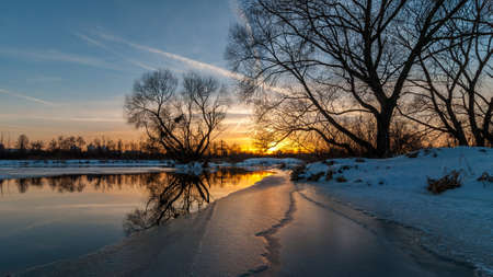 bough: Scenic evening winter landscape. beautiful glow Dramatic sunset over the river to the coast suburb under snow and ice edge. February thaw