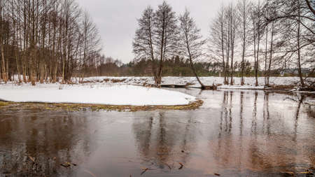 Early February thaw. Beautiful winter landscape. Small snow island on the forest river Stock Photo