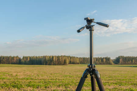 non stock: Tripod for camera in the field against the blue sky, field and forest. hobby