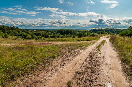 non stock: Summer landscape. rural dirt road in a hilly area under a blue cloudy sky Stock Photo