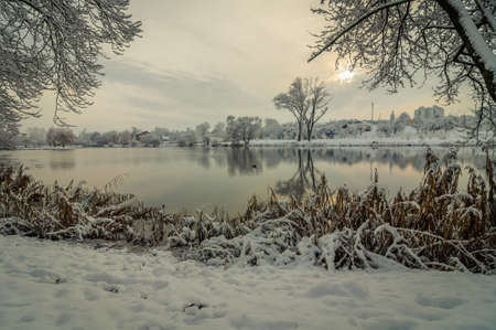 Scenic view from the snow-covered coast of the river in the winter city park Stock Photo