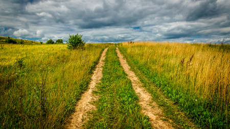 summer countryside. empty rural dirt road through grassy field under a cloudy dramatic sky Reklamní fotografie