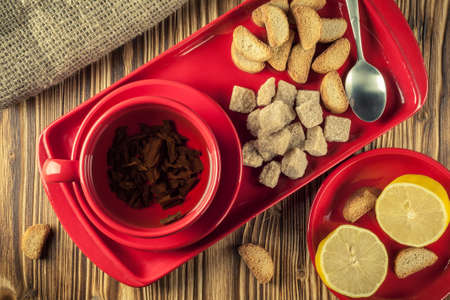 tea break. Tea in a red ceramic cup on a tray with lump reed sugar, crackers and lemon on a wooden background. top view
