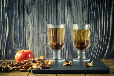 two clear glass cups of hot tea with dried fruit and fresh apple on a stone plate and a wooden background