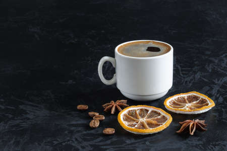 freshly brewed coffee with froth in a white cup with dried lemon slices, star anise and coffee beans on a black concrete textural background with copy space. angled side view. dark photo