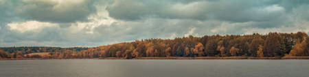 late fall variegated colors. wide panoramic view across the water surface to the opposite river bank with coastal forest under a cloudy sky on October overcast day. colorful autumn landscape