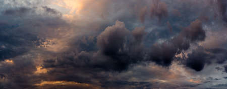 wide panoramic view of the dramatic sunset sky with heavy dark cumulus clouds and natural purple-orange lighting from the evening dawn. picturesque artistic backdrop for atmospheric design, decoration
