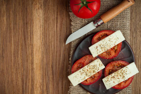 sliced fresh tomatoes under cheese with mediterranean spices on a clay plate on a burlap napkin on an old textured wooden surface. artistic mockup with copy space. top view