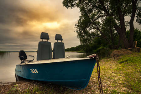summer evening coastal walk. metal fishing or pleasure boat on the grassy shore of a large lake under a dramatic cloudy sky with a warm skylight, trees and shallow water