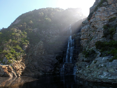 rise above: The sun is just starting to rise above the headland at Storms River Waterfall in South Africa