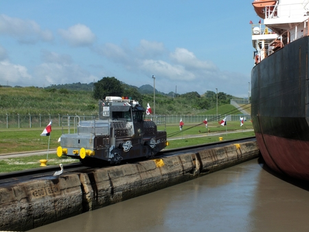 panama flag: One of the 290 HP locomotives are used to keep ships in position in the locks. They are essential for a safe and expeditious transit of the Panama Canal, and run on two tracks along the lock walls from one end to the other.