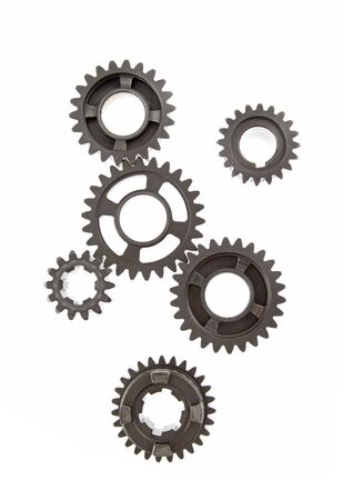 linked: Solid metal gears linked together on white background. Stock Photo