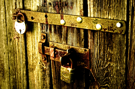 padlocks: Old padlocks securing an old door