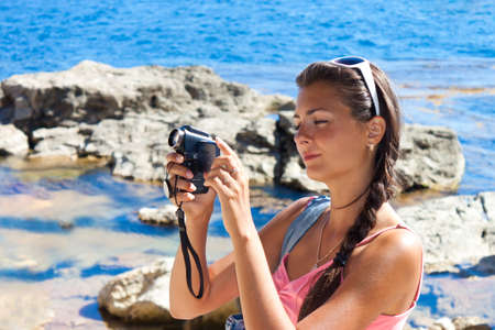 Beautiful girl with a camcorder on the sea shore photo