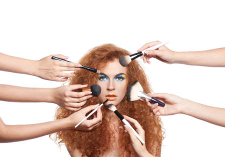 makeup brushes: Portrait beautiful red long wavy, curly hair girl with make-up brushes near attractive face, many hands apply make up on woman face, beauty cosmetic hairstyle concept isolated over white background Stock Photo