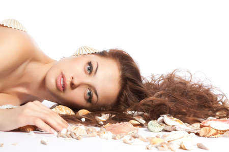 water nymph: pretty young woman with long red curly hair lying on the floor beach, sea shell with marine cockleshell, isolated over white background. Concept freshness, Spa resort Stock Photo