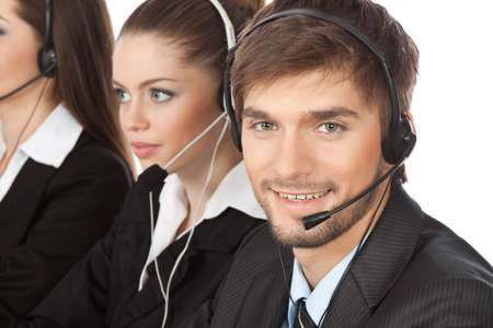 Attractive Smiling handsome positive young businessman and colleagues in a call center office, support phone operators with headset at workplace over white background, agent friendly looking at camera Stock Photo - 10414147