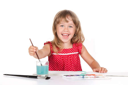 making a face: young attractive little happy smiling 4 years girl with paint sitting at the table, desk isolated over white background, looking at camera