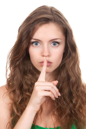 portrait of attractive teenage girl with finger on lips, photo