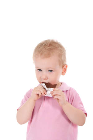 Little boy holding chocolate bar over white background photo