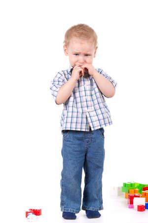 child crying: niño llorando de pie, cerca de los juguetes sobre fondo blanco Foto de archivo