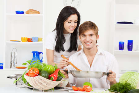 young lovely couple in their kitchen coocking happy smile Stock Photo - 13044403