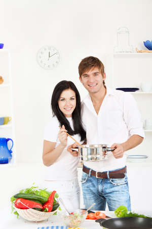 vegetables young couple: young lovely couple in their kitchen coocking happy smile