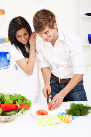 young lovely couple in their kitchen coocking happy smile photo