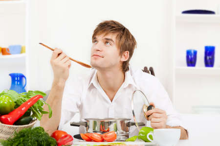 young handsome man coocking on kitchen happy smile photo
