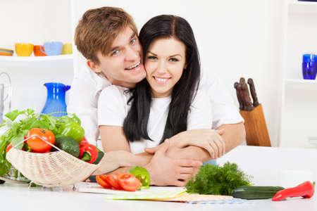 desayuno romantico: pareja joven hermosa en la cocina coocking sonrisa feliz