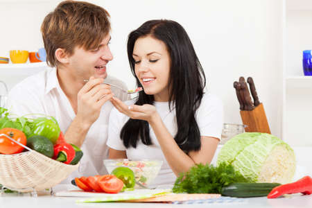 young lovely couple in their kitchen coocking happy smile Stock Photo - 13044424